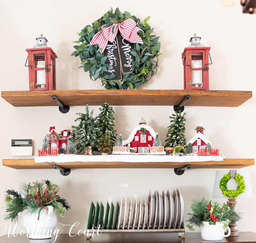 Shelves decorated for Christmas with a Christmas village and plaid dishes