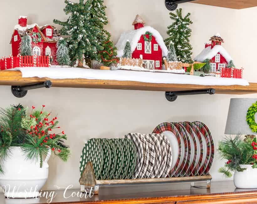 Plate rack on top of sideboard filled with Christmas plaid dishes.