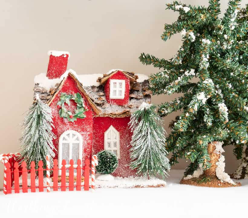 Red Christmas mini house on a bed of faux snow
