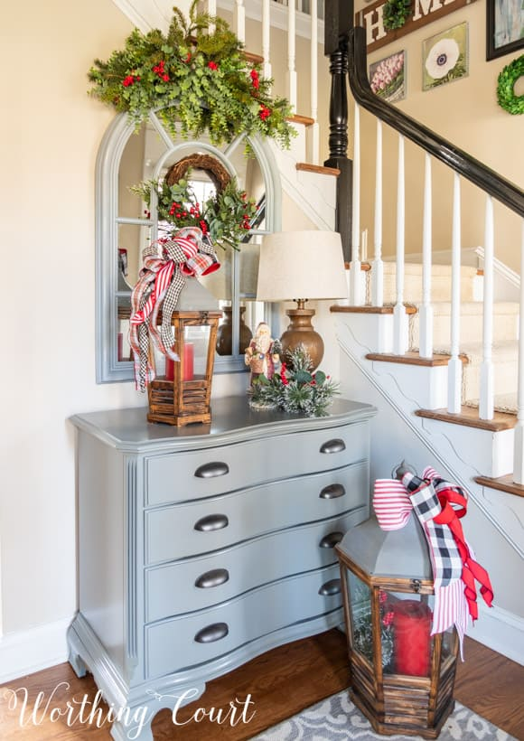 Small gray chest with an arched mirror above with a faux greenery swag and Christmas decorations