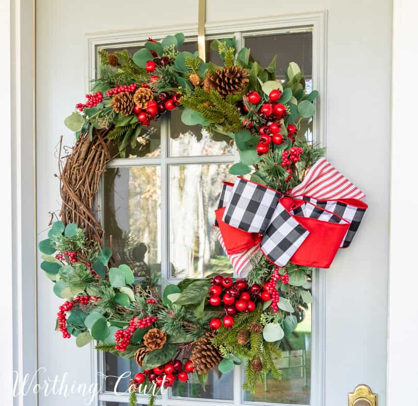 An up close picture of the berry and greenery wreath with a large red, black and white bow on the side.