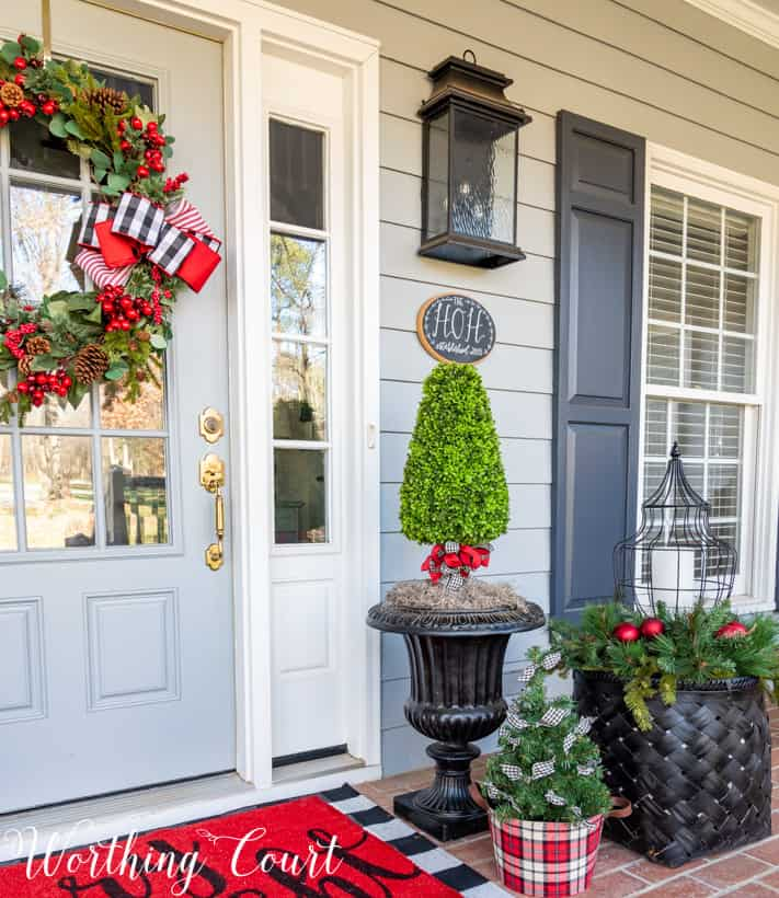 A mini Christmas tree is in a plaid container beside a black basket on the front porch.