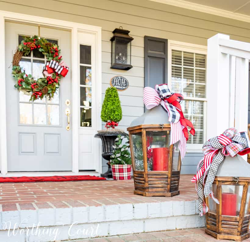 Lanterns with Christmas ribbon and red candles on front porch steps.