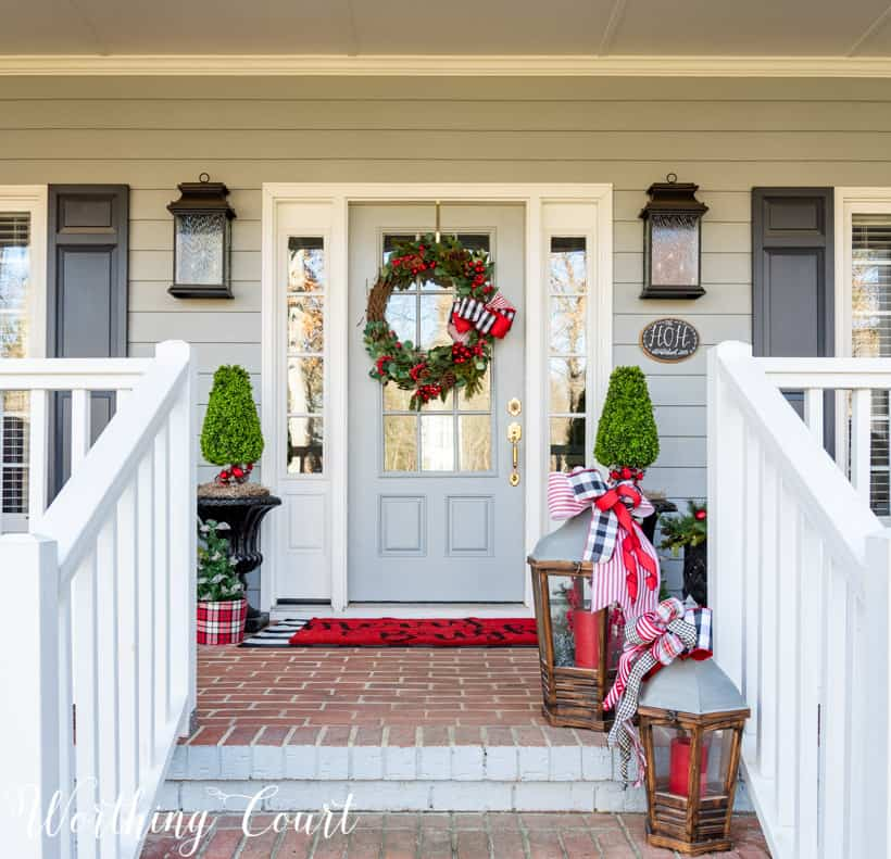 front porch decorated for Christmas with red and green