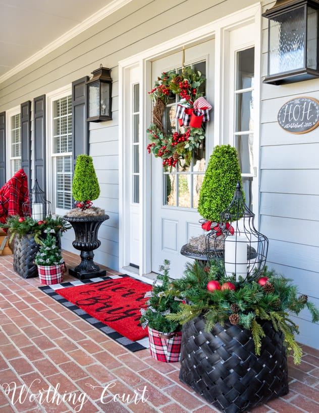Front porch decorated for Christmas with red and green.