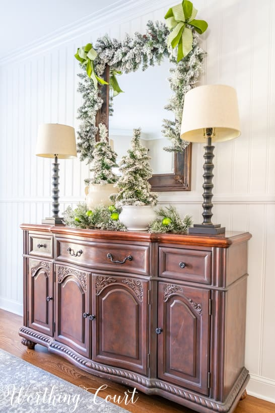 sideboard with mirror above with flocked garland, flocked mini trees and green ribbon