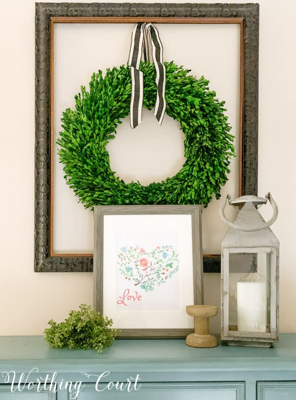 The Valentines printable on a side table with a green wreath on the wall above it.
