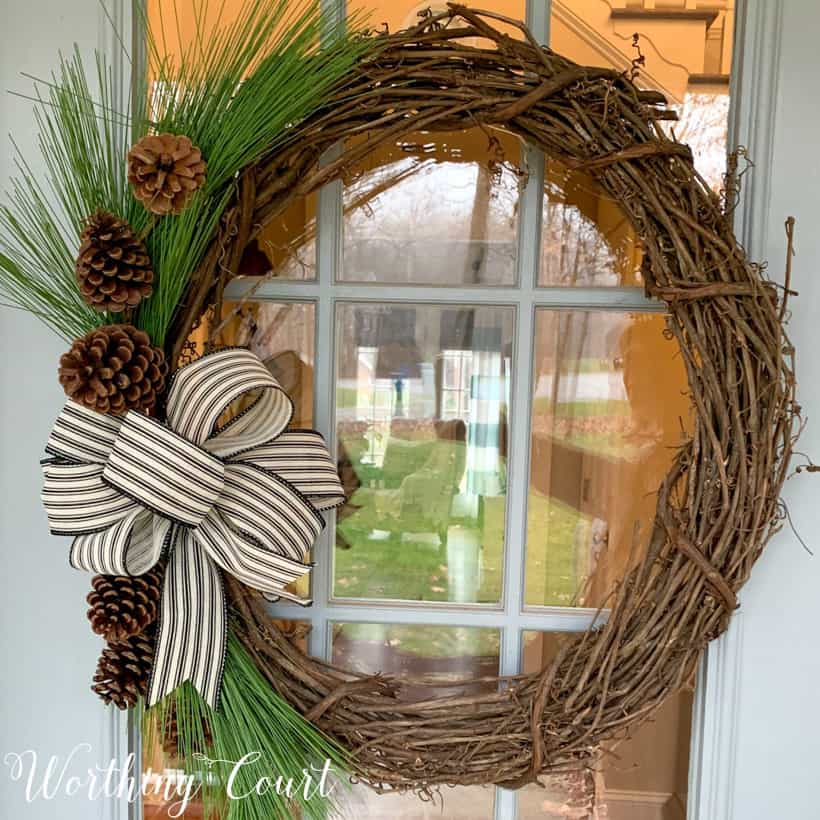 grapevine wreath with pine branches and black and white bow