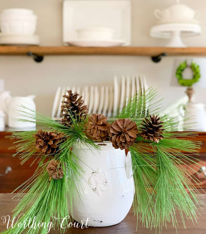 white vase filled with faux pine branches