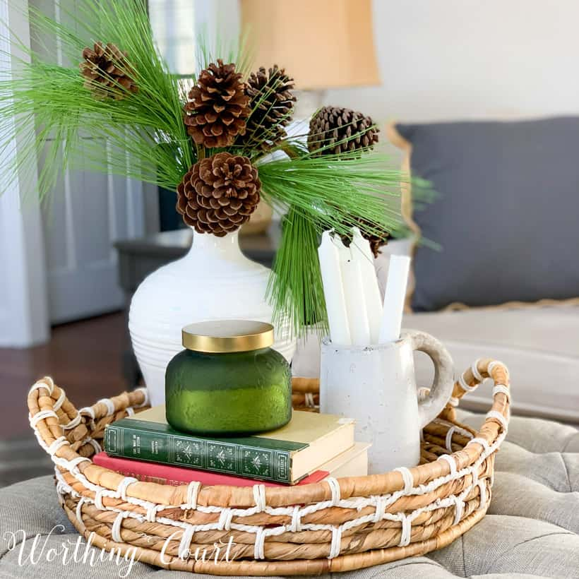 woven tray with white vase filled with evergreens