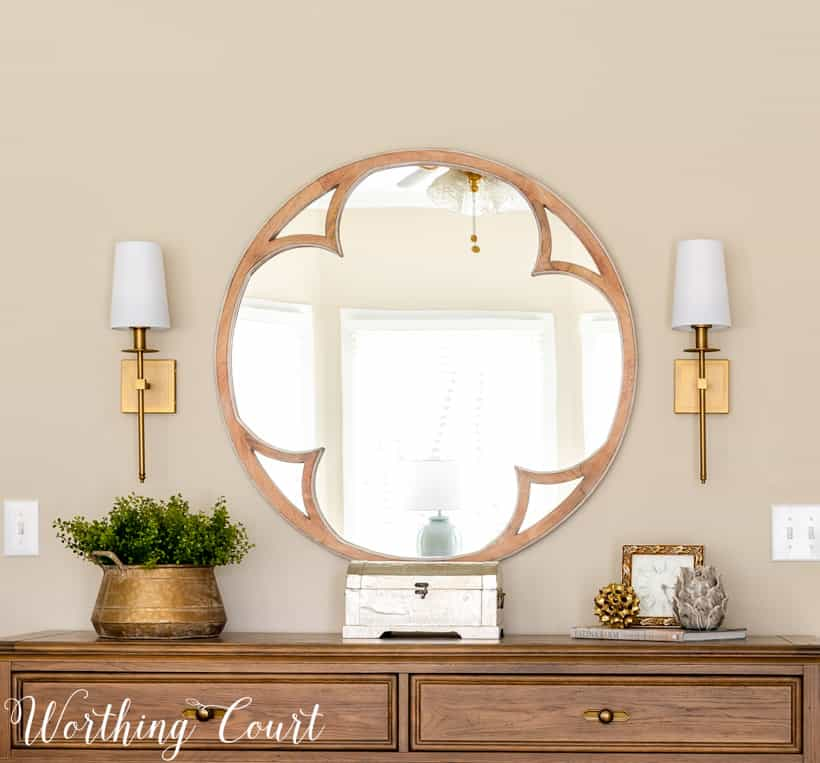 round mirror above dresser flanked by brass sconces