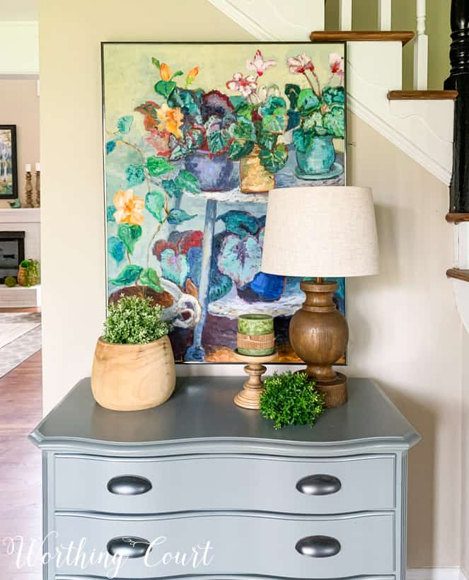 colorful oil painting hanging above gray chest