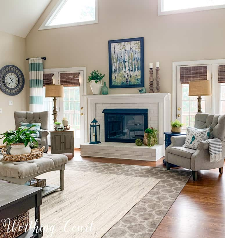 fireplace decorated for spring flanked by two gray chairs