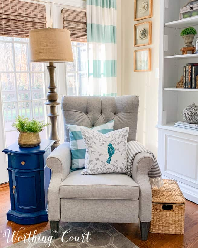 gray chair with two blue and white pillows