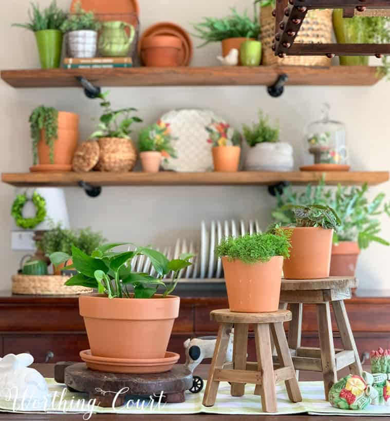 table centerpiece with terra cotta pots and greenery displayed at different levels