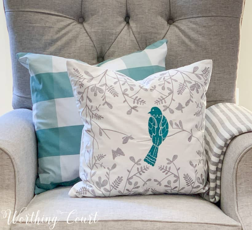 two blue and white spring pillows on a gray chair
