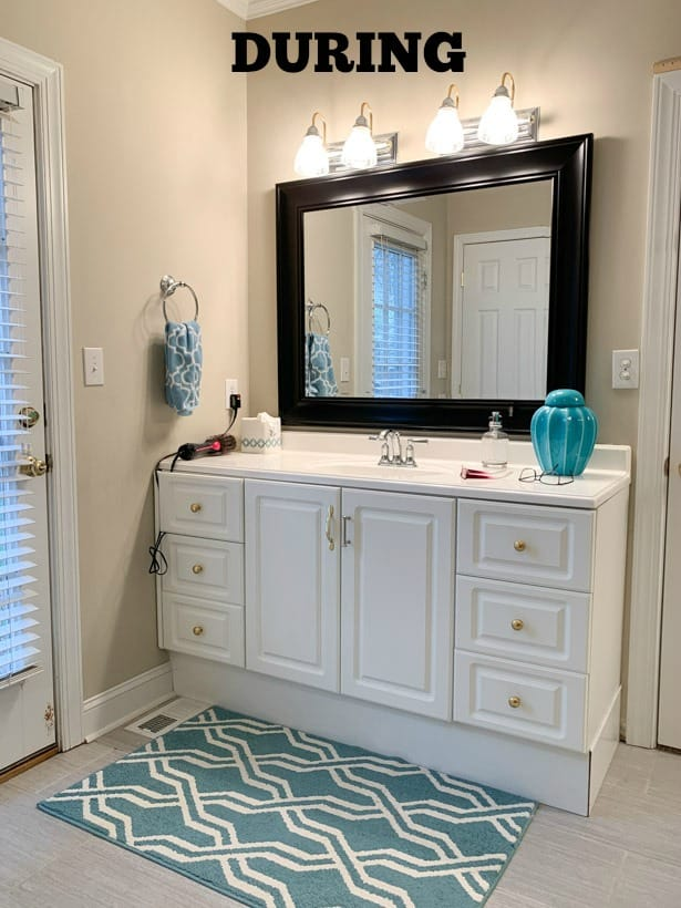 A look at the bathroom during the renovation with a white vanity and blue and white rug.