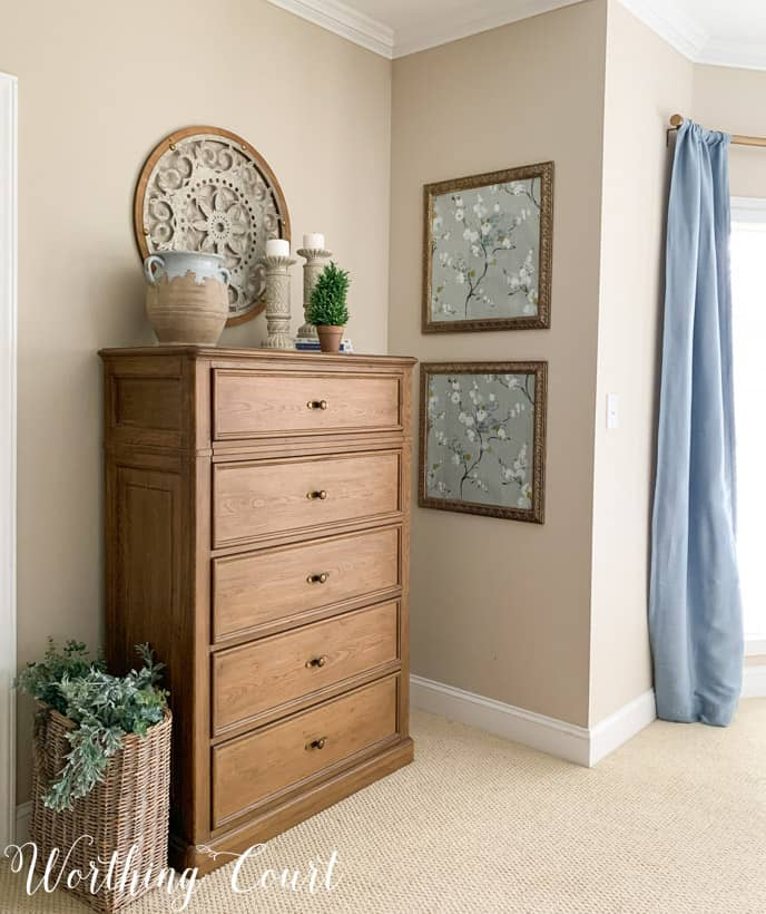 master bedroom chest of drawers with blue draperies and framed wallpaper