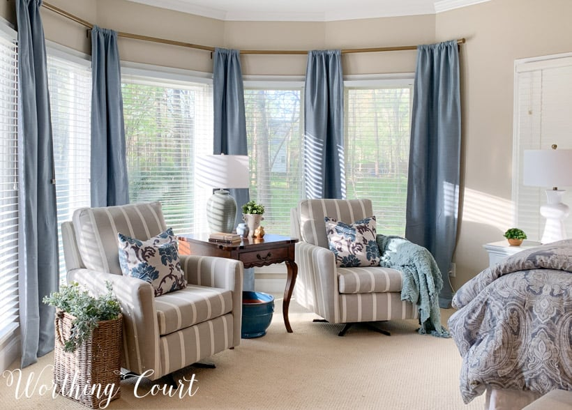 bedroom bay window sitting area with chairs and blue draperies