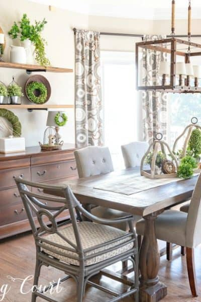 breakfast room with table, chairs and open shelves decorated for spring