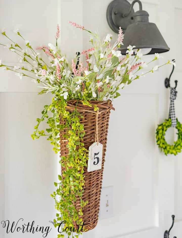 wicker basket filled with faux florals hanging on the wall