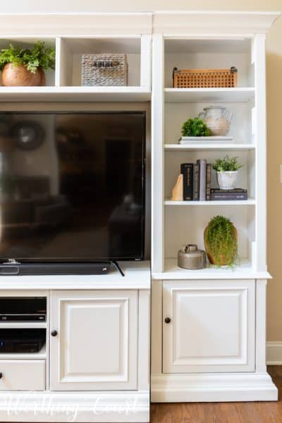 portion of white entertainment center with accessories