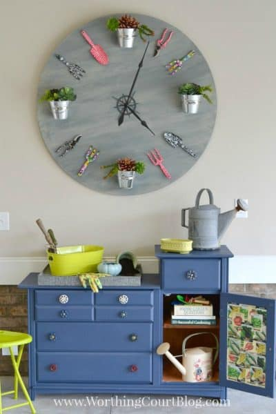 huge diy clock above blue garden bench