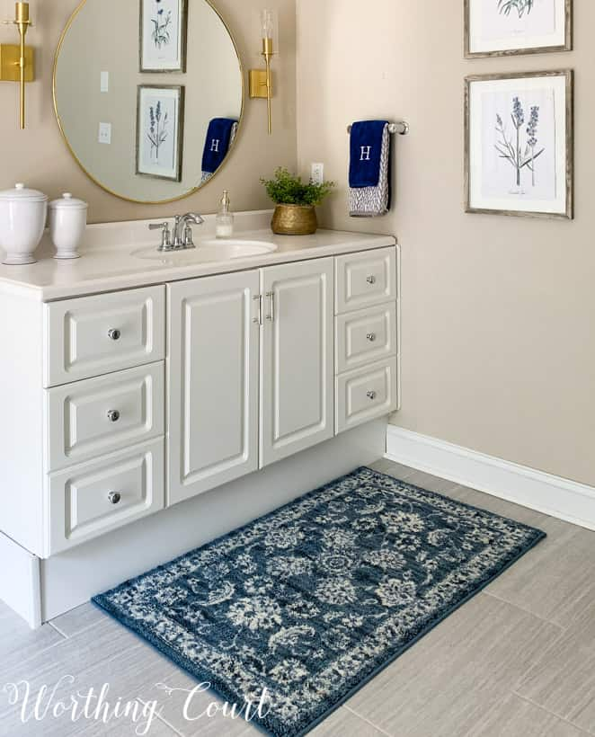 blue bath mat in front of white bathroom vanity