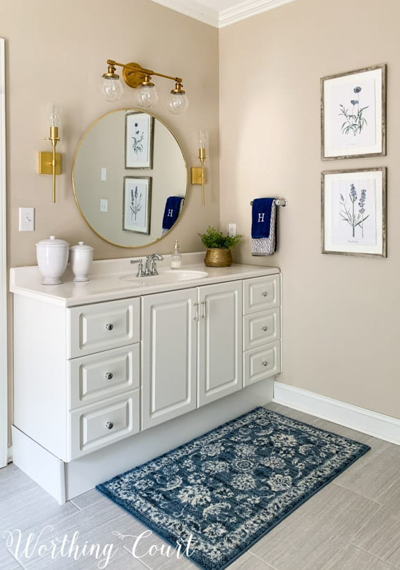 white bathroom vanity with round mirror, gold lights and accessories