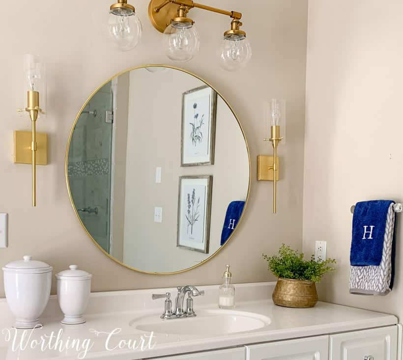 master bathroom vanity with round mirror and accessories