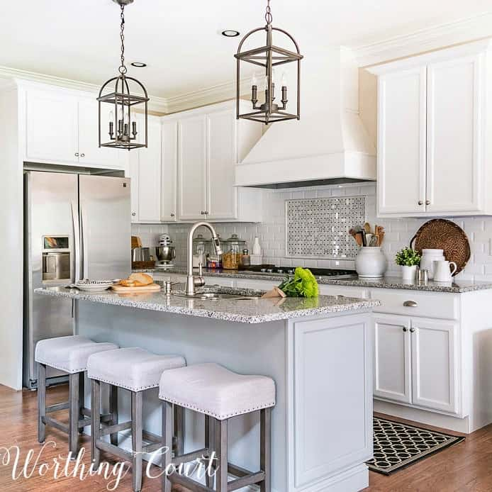 kitchen with white shaker cabinets, gray island, large hood and stainless refrigerator