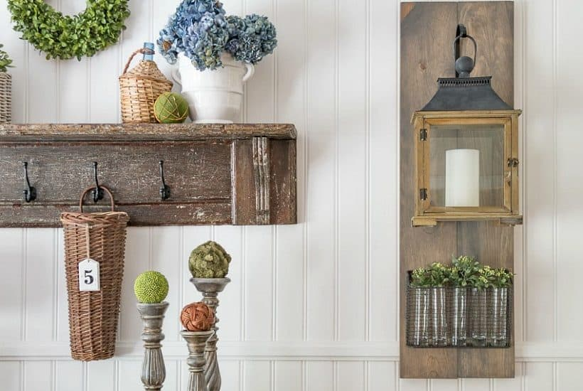 white paneled wall with hanging lantern and vintage shelf display