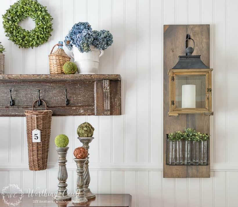 white paneled wall with hanging lantern and vintage shelf display