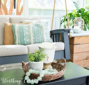 Vignette in a basket on a coffee table with a porch swing and side table in the background