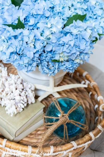 blue hydrangeas in a white vase in a wicker tray on coffee table