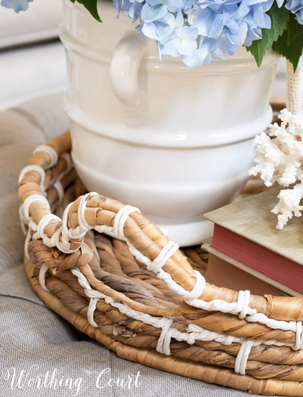 wicker tray on a coffee table containing a summer vignette
