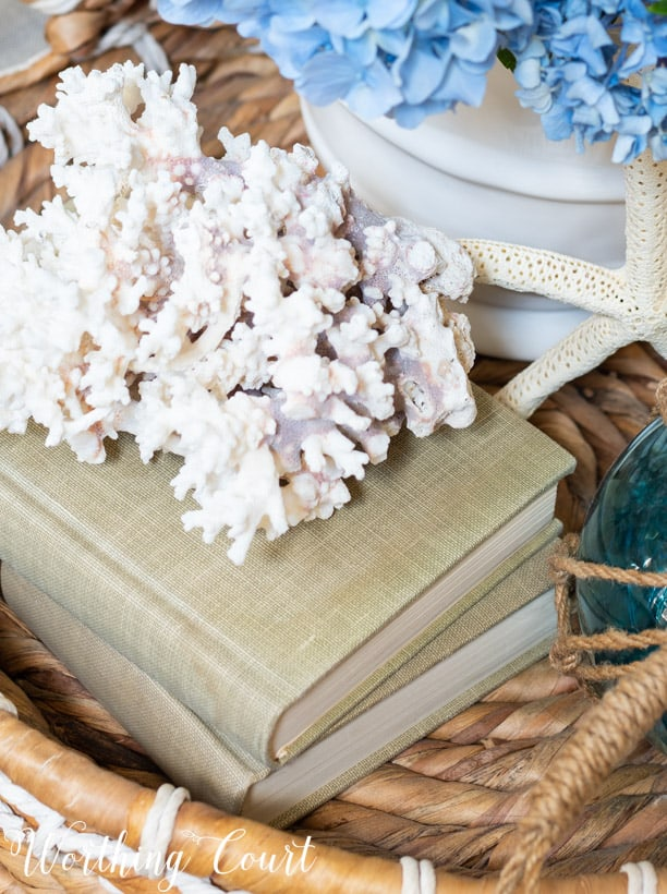 summer vignette with piece of white coral in a wicker tray on coffee table