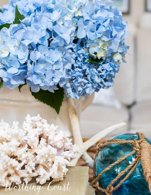 blue hydrangeas in a white vase in a wicker tray on coffee table.