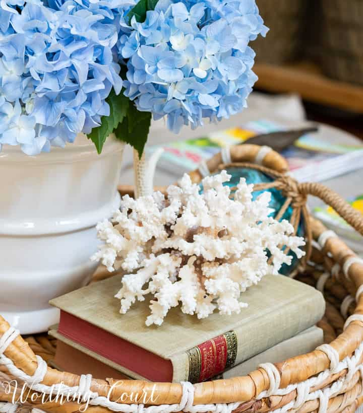 summer vignette with blue hydrangeas in a white vase in a wicker tray on coffee table