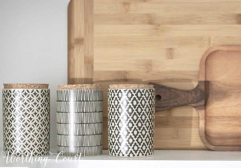 wooden cutting boards with black and white canisters in front