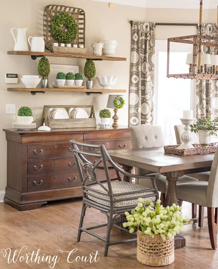 dining area with sideboard with open shelves above decorated with green and white accessories
