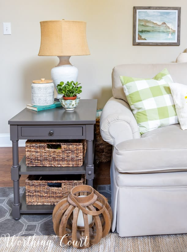 gray end table with baskets and summer accessories