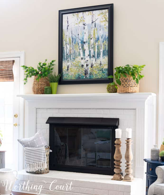 white brick fireplace with art, plants and baskets
