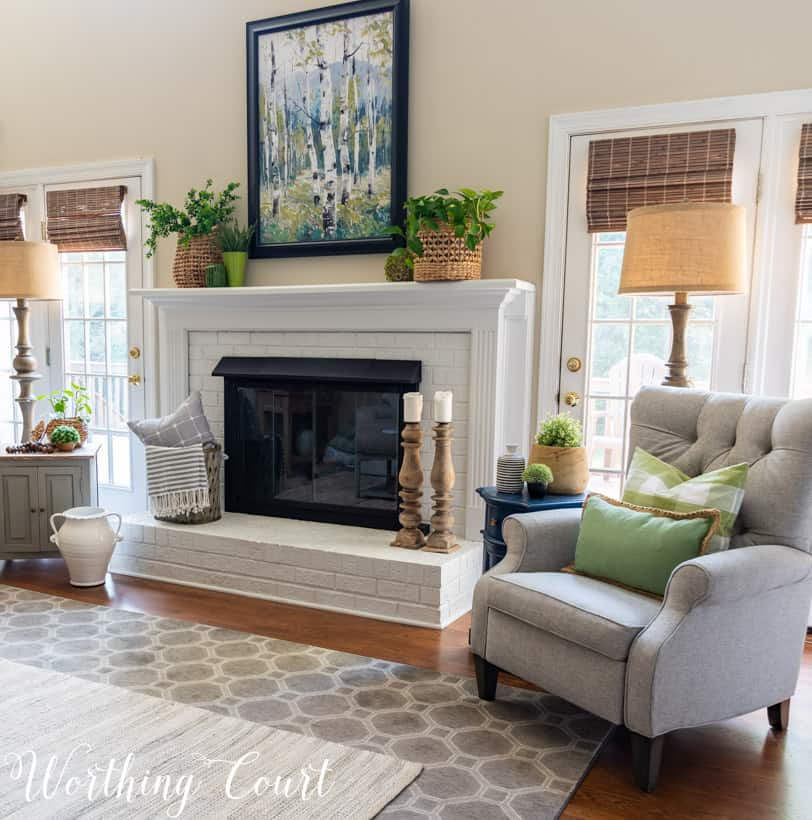 white brick fireplace with art, plants and baskets flanked by two recliners