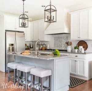 kitchen with white cabinets and gray island and stools