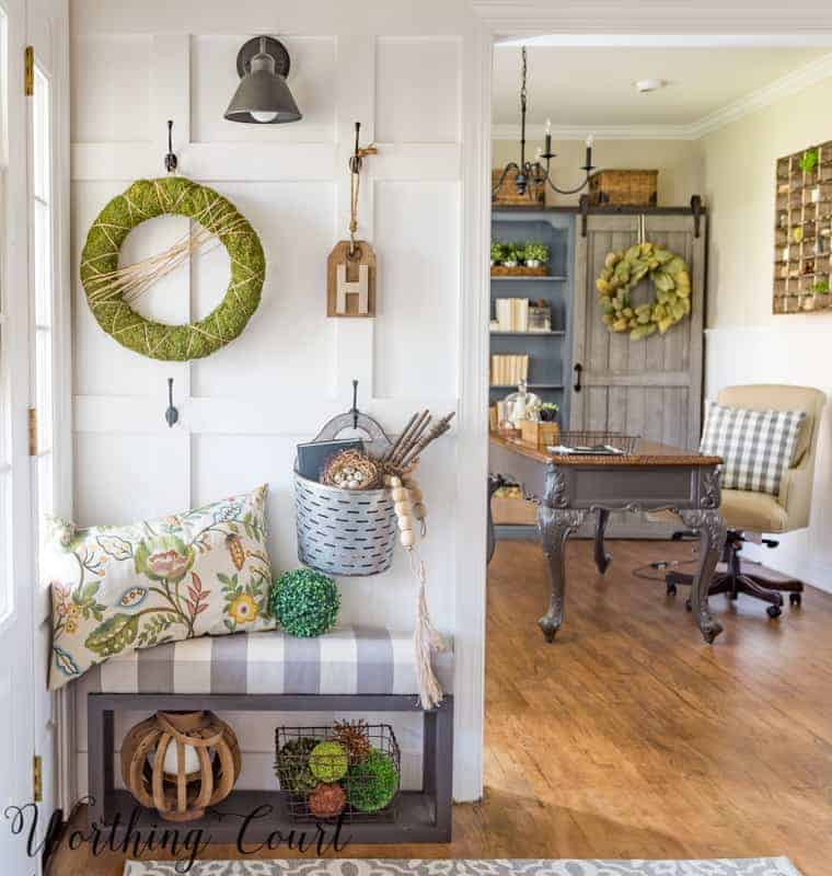 wall in foyer with doorway looking into home office with furniture and decor