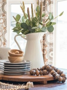 table centerpiece with white pitcher filled with greenery and wood beads on a tray