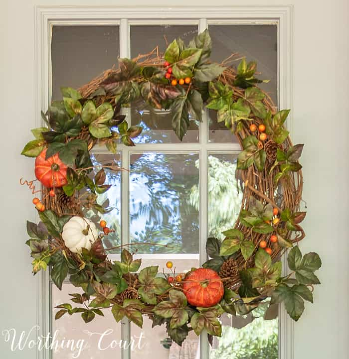fall wreath with greenery, pumpkins and berries