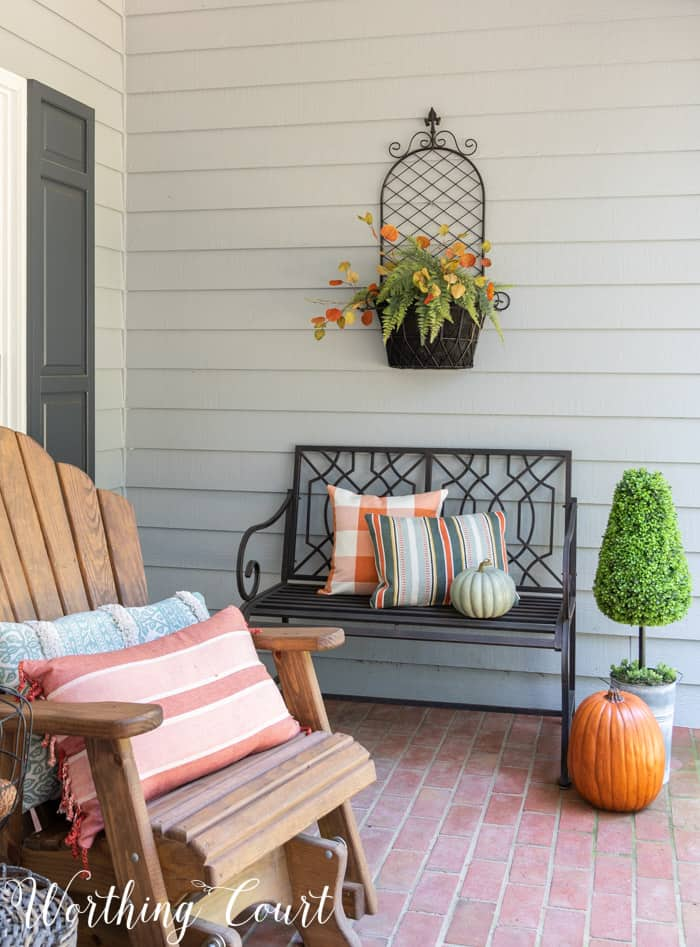 black outdoor bench with fall pillows and pumpkins