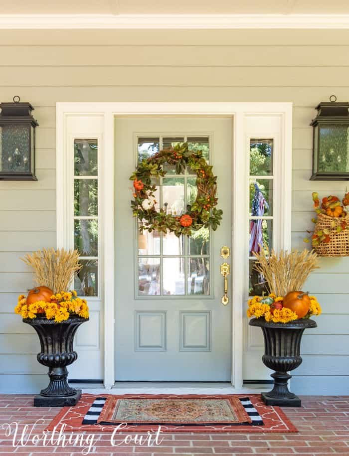 gray front door with fall wreath flanked with matching fall planters